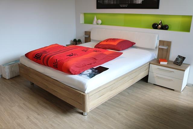 postel, červené povlečení, polička, stolky